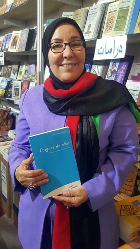 السيد فاطمة حقيق تحمل الترجمة الفرنسية لديوان قبضة حلم، للشاعر عمرعبدالدائم (الصورة: صفحة السيدة فاطمة حقيق).